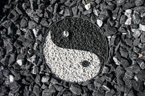 Yin and Yang designed with stone in a outdoor garden Yin and Yang designed with stone in a outdoor garden surrounding the sign taoism stock pictures, royalty-free photos & images
