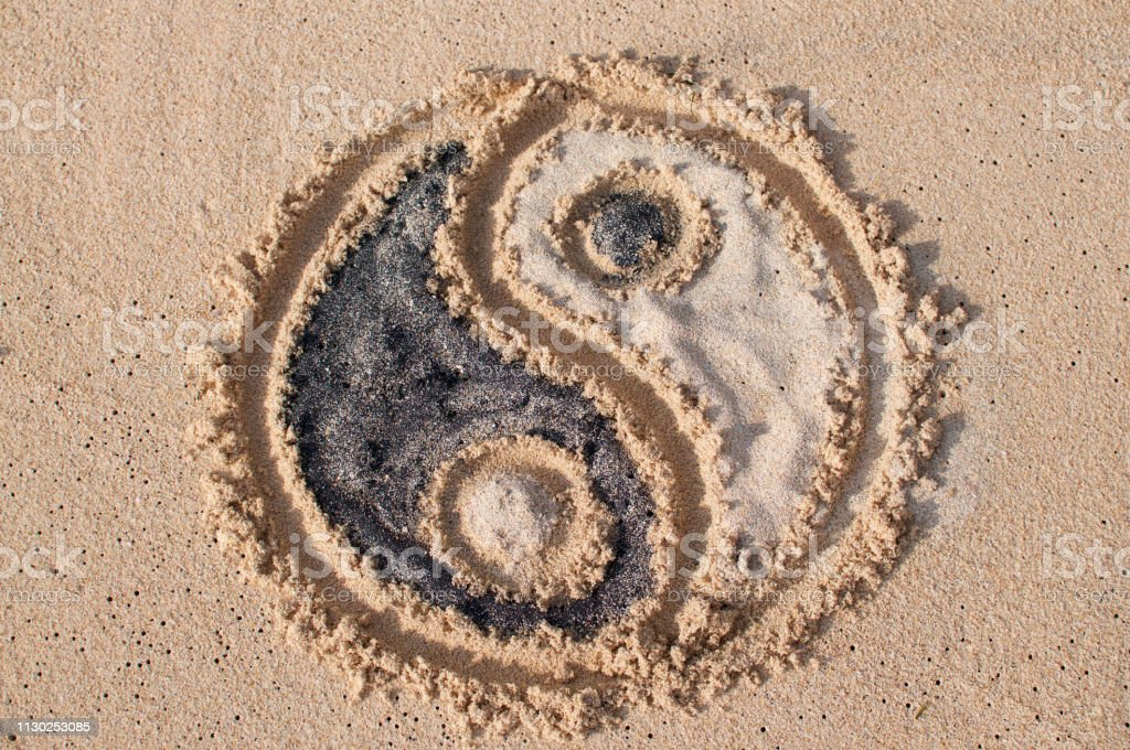 Yin-yang symbol drawn and filled with black and white sand at Melasti...