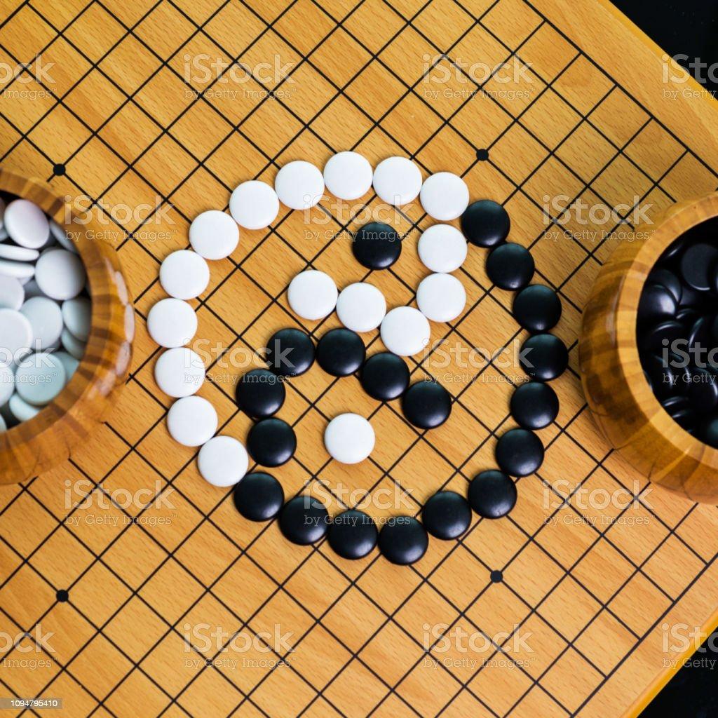 Yin yang symbol on go game board.