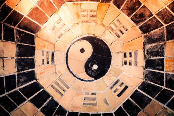 yin yang symbol. yin yang symbol on tiled wall with sunlight tone. taoism stock pictures, royalty-free photos & images