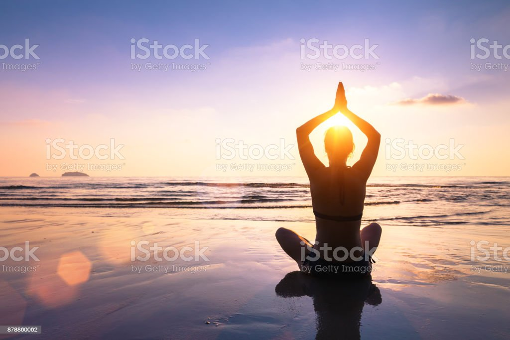 Yoga and meditation calm peaceful beach sunset fit young woman stock photo