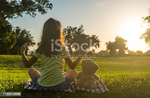 Little girl practicing yoga at sunset with her teddy bear.