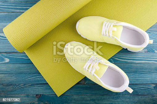 637596492istockphoto Yoga and sport concept. Yoga mat and sport shoes on wooden background. Top view 821977062