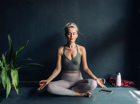 Practicing self isolation: woman with wireless earphones doing yoga in the comfort of her home.