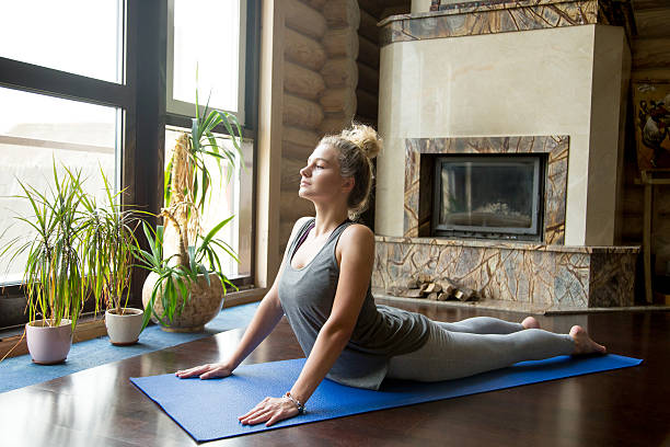 Yoga at home: Cobra Pose Full length portrait of attractive young woman working out at home in living room, doing yoga or pilates exercise on blue mat, pose for flexible spine cobra pose stock pictures, royalty-free photos & images