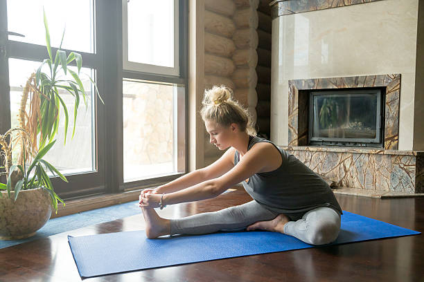 Yoga at home: Janu Sirsasana pose Full length portrait of attractive young woman working out at home in living room, doing yoga or pilates exercise on blue mat, sitting in Janu Sirsasana, head-to-knee forward bend posture hamstring stock pictures, royalty-free photos & images