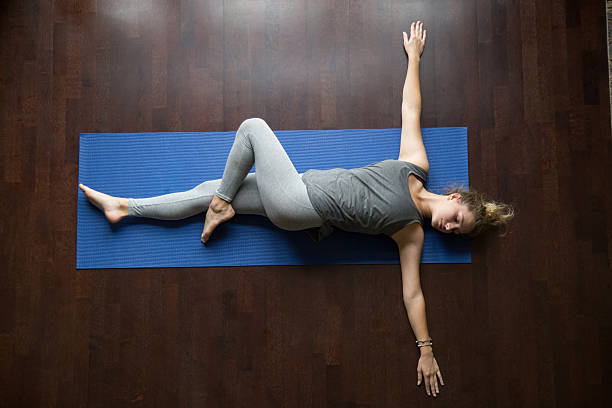 Yoga at home: Jathara Parivartanasana Pose Attractive young woman working out indoors, doing yoga exercise on wooden floor, lying in Reclining Spinal Twist, Jathara Parivartanasana, resting after practice, full length, top view lying on back stock pictures, royalty-free photos & images