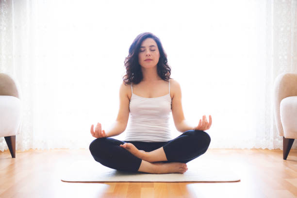 Yoga at home. Keep calm. Attractive young woman sitting on lotus position on floor with eyes closed. stock photo