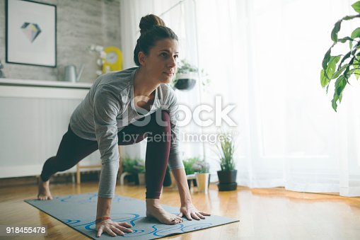 Young woman practicing iyengar yoga at home in her living room.