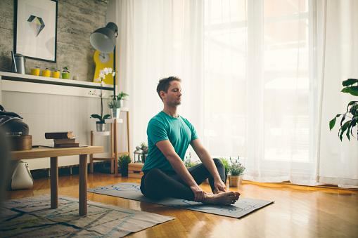 Mid adult man practicing iyengar yoga in his home. Baddha Konasana. Butterfly Pose.