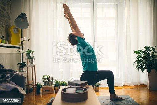 Mid adult man practicing iyengar yoga in his home. Anjaneyasana. Low Lunge.