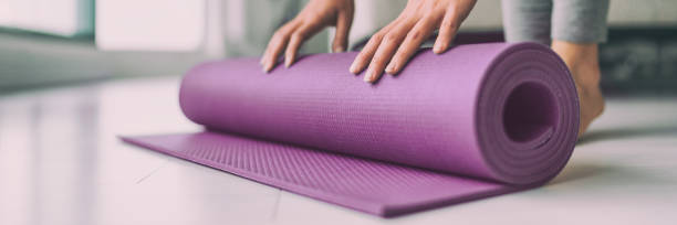 Yoga at home woman rolling pink exercise mat in living room starting warm up meditation zen well being wellness banner panoramic apartment living room lifestyle stock photo
