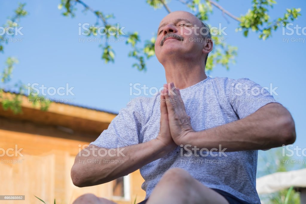 Yoga at park. Senior man with mustache with namaste sitting.Concept of calm and meditation. stock photo