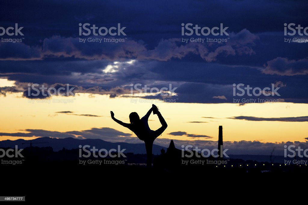 Yoga at sunset Silhouette of a girl enjoying the golden sunset. Activity Stock Photo