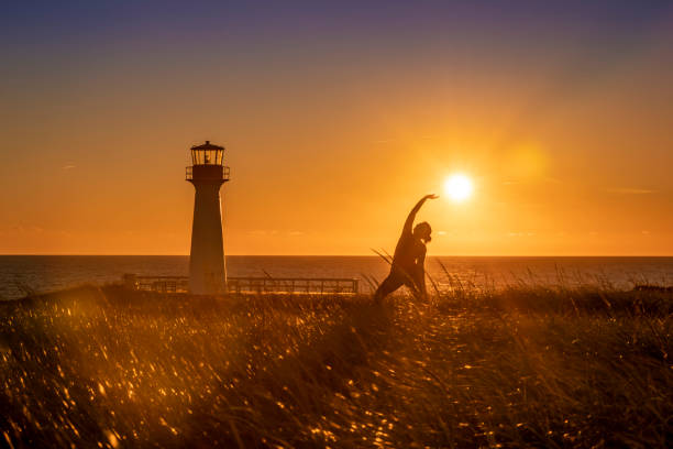 Yoga at the foot of the lighthouse stock photo