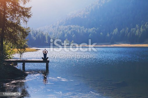 yoga beautiful background, harmony in life, meditation practice, silhouette of woman sitting in lotus position on the pier of lake and doing breathing exercises in beautiful landscape