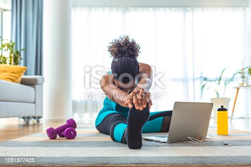 Fit woman high body flexibility stretching her leg and back to warm up doing aerobics gymnastics exercises at home.