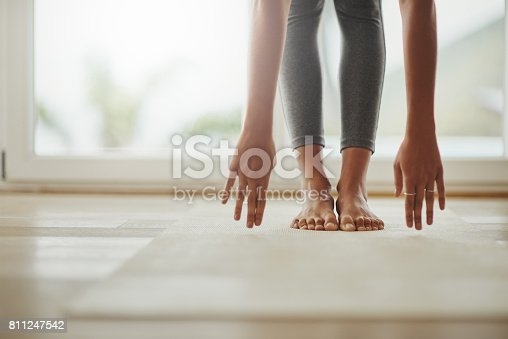 Cropped shot of a young woman practicing yoga at home