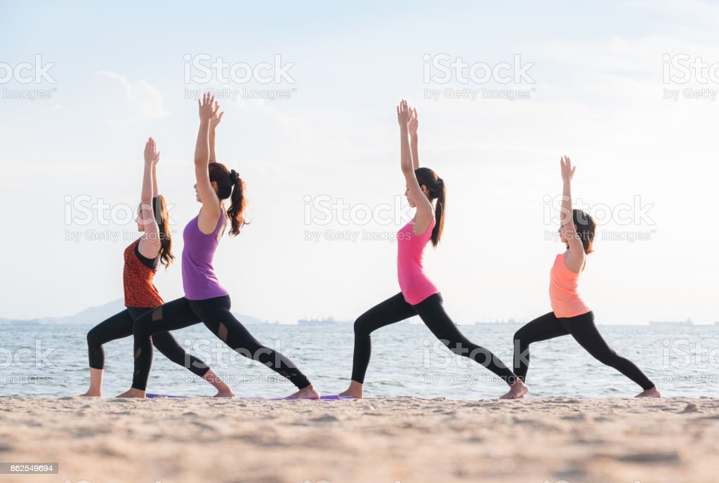 Yoga class at sea beach in evening ,Group of people doing Warrior poses with clam relax emotion at beach,Meditation pose,Wellness and Healthy balance lifestyle. stock photo