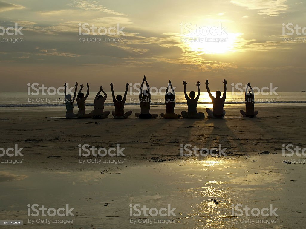 Yoga class at sunset by the ocean stock photo