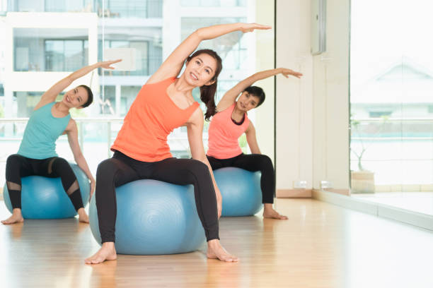 Yoga class in studio room,Group of people doing yoga pose with training ball, stretching pose,Wellness and Healthy Lifestyle Yoga class in studio room,Group of people doing yoga pose with training ball, stretching pose,Wellness and Healthy Lifestyle. yoga instructor stock pictures, royalty-free photos & images