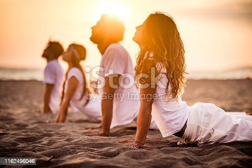 Group of people exercising Yoga in cobra pose on a beach at sunset. Focus is on woman in the foreground.