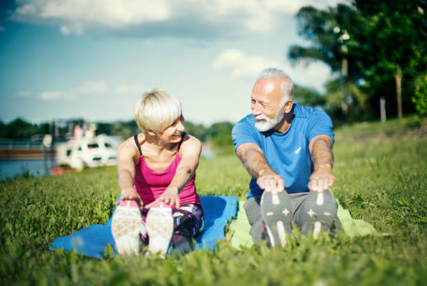 Yoga class outdoors. Senior couple stretching together outdoors. Smiling and looking at camera. touching toes stock pictures, royalty-free photos & images