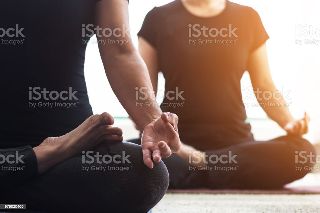 Yoga class people lifestyle with women group in lotus pose meditating in relax silence gym studio indoor in the morning, practicing body mind soul balance stock photo