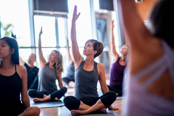 Yoga Class A group of women are indoors in a fitness center. They are raising their arms while doing yoga. yoga studio stock pictures, royalty-free photos & images