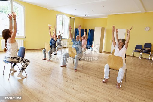 Senior woman in yoga class, sitting on chairs and exercising, they have arms raised and looking up to hands, the room has yellow painted walls