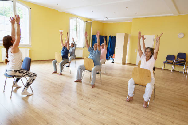 zajęcia jogi: starsze kobiety ćwiczące na krześle - krzesło zdjęcia i obrazy z banku zdjęć