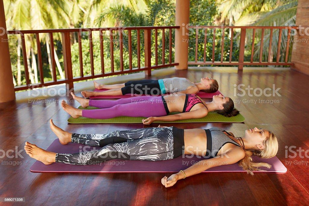 Yoga class with women lying on floor , Savasana stock photo