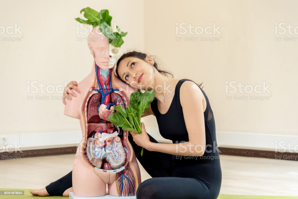 A yoga coach sits next to a medical dummy stock photo
