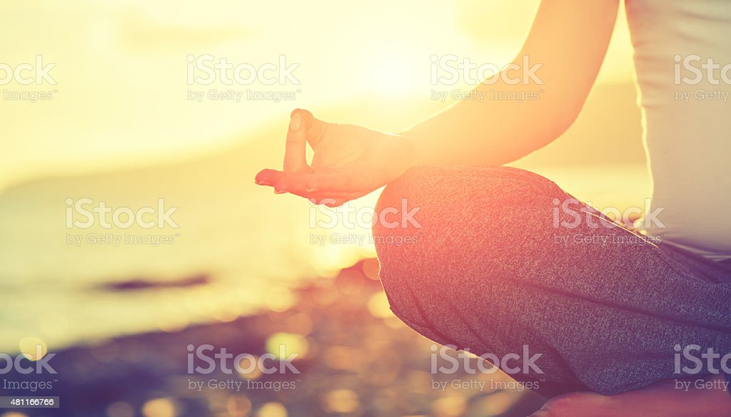 Yoga concept. hand woman practicing lotus pose on beach stock photo