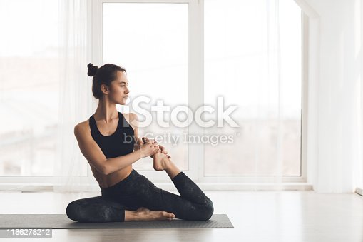 Yoga concept. Sporty woman stretching on mat over light panoramic windows, free space