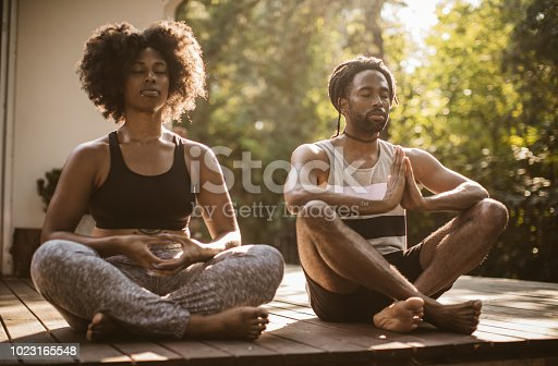 Young couple practicing yoga outdoors on porch, they enjoy in summer sun and meditation