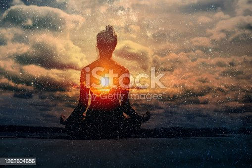Yoga day concept. Multiple exposure image. Clouds and sun. Pranayama in lotus asana