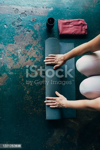Hands of an anonymous woman preparing for her home yoga practice.