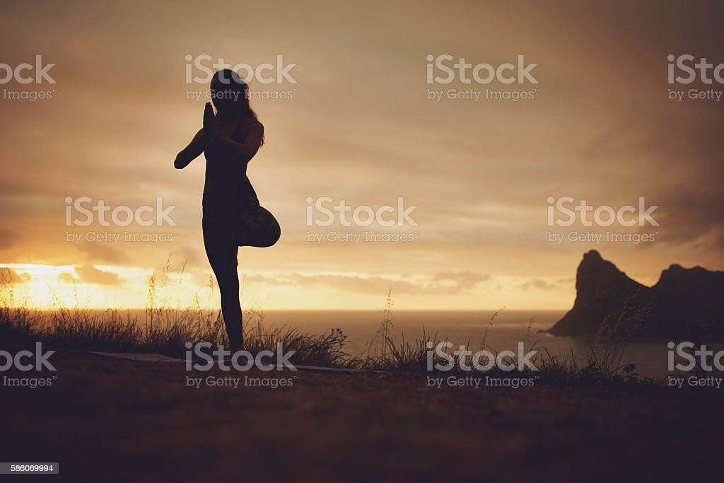 Yoga exercise on the cliff stock photo