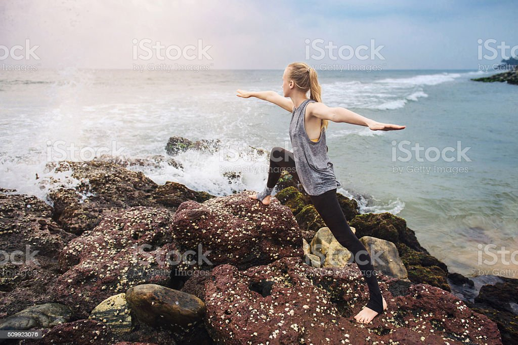 Yoga exercise on the sea cliff on sunset stock photo