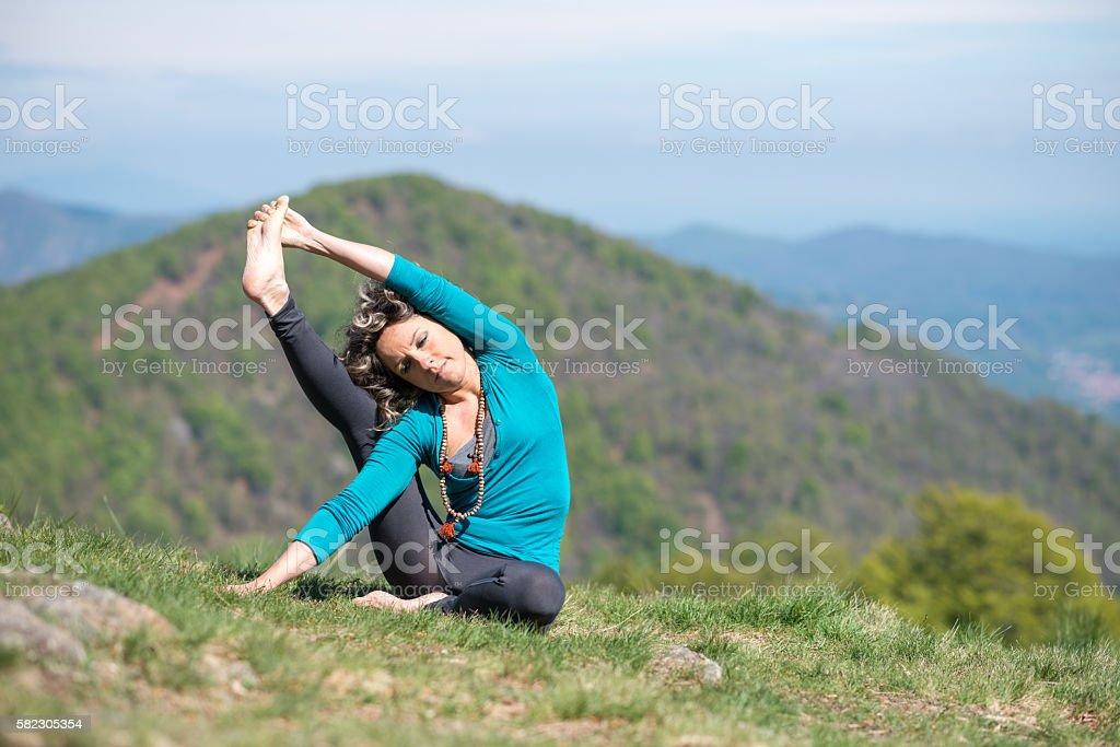 Yoga exercises in nature: Urdhva Parivrrta Janu Sirsasana III stock photo