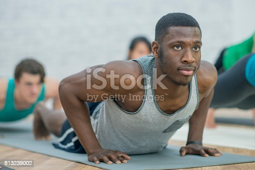 A multi-ethnic group of people are doing yoga and stretching inside a fitness centre. A man of African descent is leading the group. He is doing an upright yoga pose on the floor.