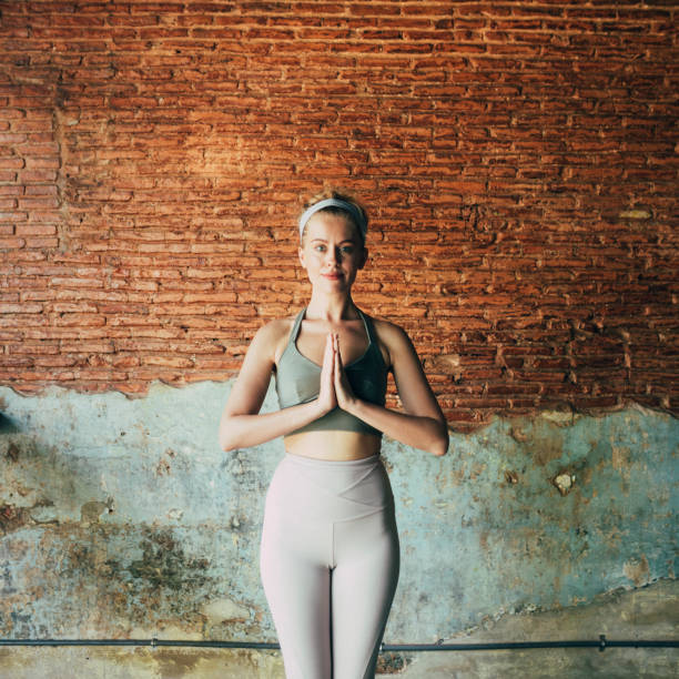 Yoga for Inner Peace: Woman in the Namaste Yoga Position Beautiful woman in sportswear doing yoga at home. prayer pose yoga stock pictures, royalty-free photos & images