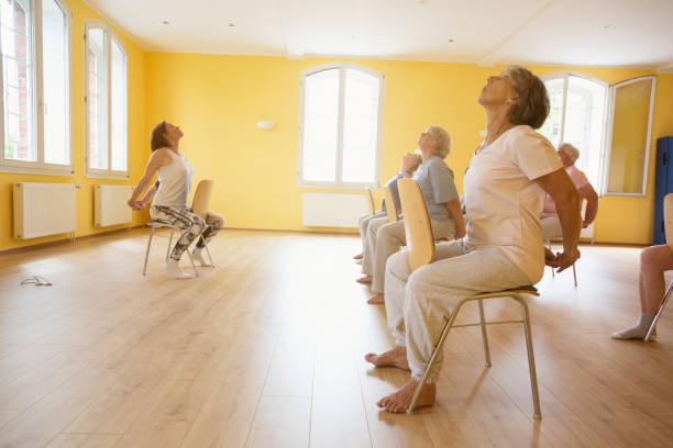 Yoga for seniors: exercising on chairs stock photo