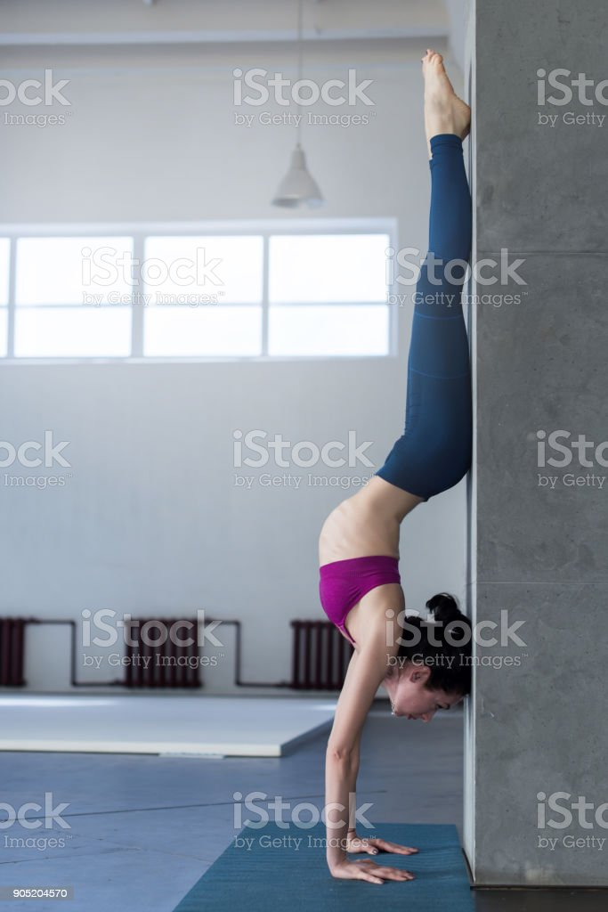 Yoga girl doing handstand with backbend exercise in gym stock photo