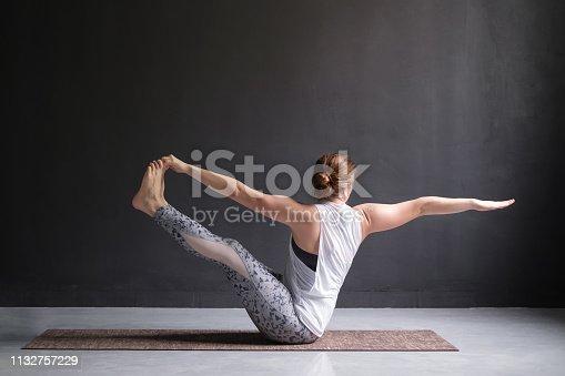 Yoga woman doing parivrtta navasana or twisted boat pose