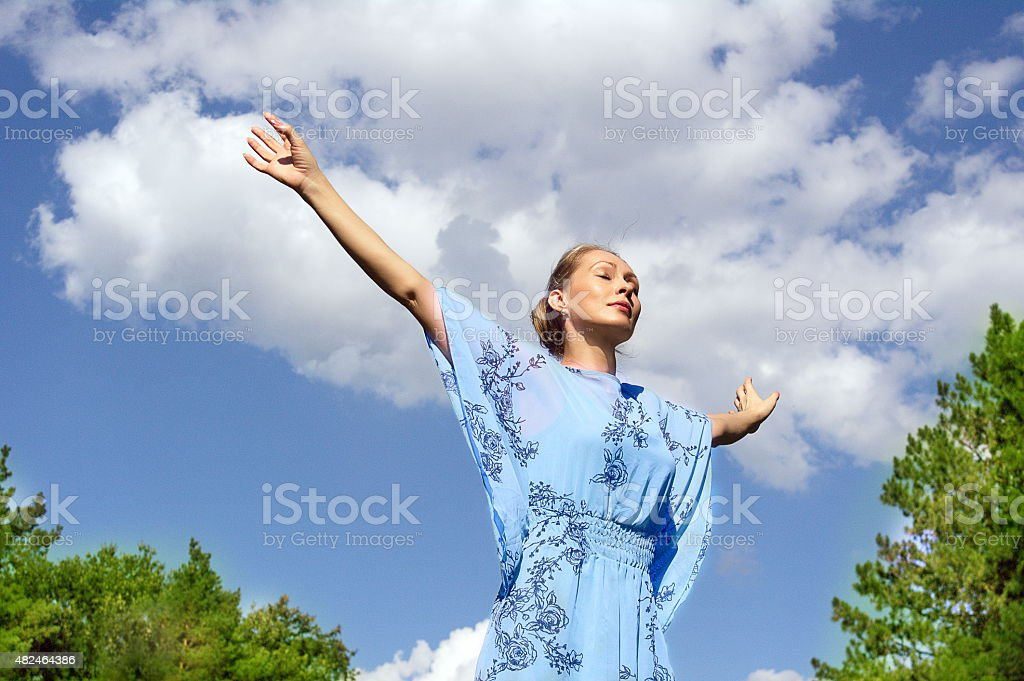 Yoga girl fly under blue sky in green field stock photo