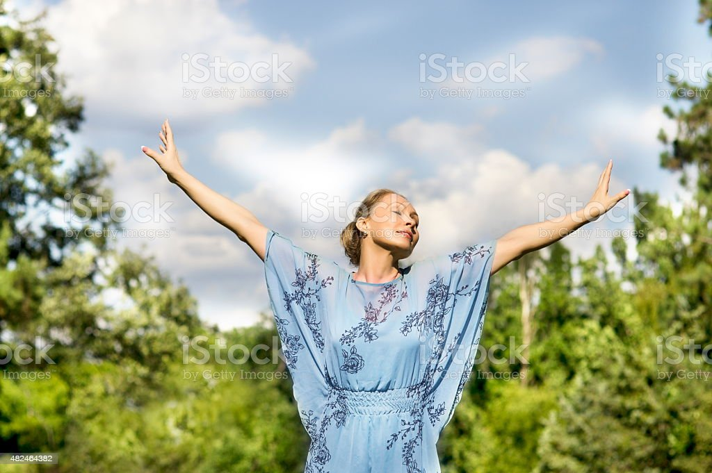 Yoga girl fly under blue sky in green forest stock photo