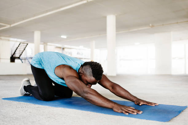 Yoga happens anywhere, anytime Shot of a handsome and sporty young man doing yoga in an underground parking lot childs pose stock pictures, royalty-free photos & images