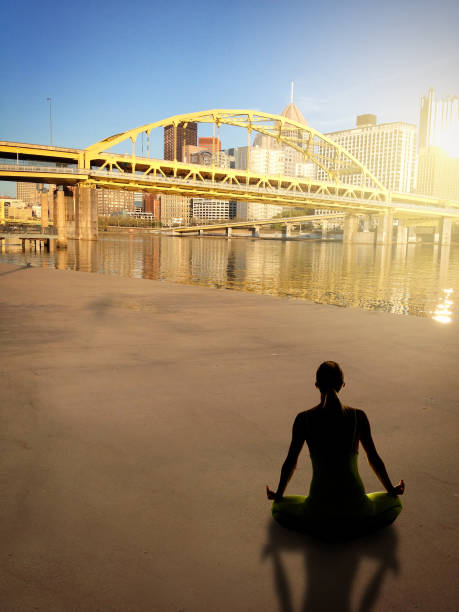 Yoga In Pittsburgh Pennsylvania A silhouette of a woman meditating by the Allegheny River near downtown Pittsburgh, Pennsylvania, USA. pittsburgh bridge stock pictures, royalty-free photos & images
